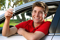 teenage boy sitting in driver's seat holding keys