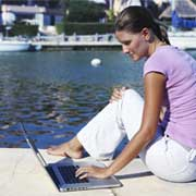 woman using a laptop by a lake